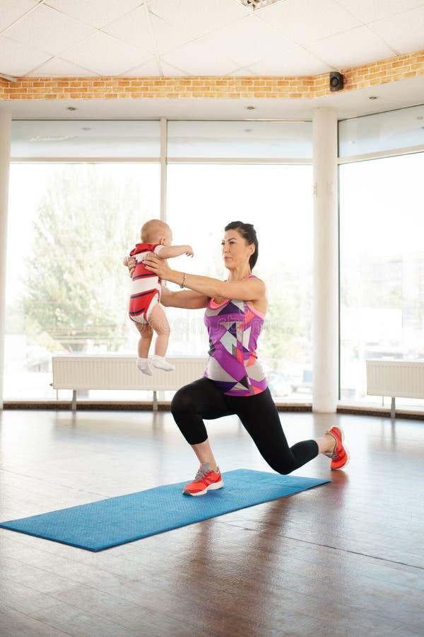Sporta mum w sportów ubraniach ćwiczenia z dzieckiem zdjęcie stock