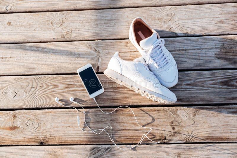 Sporta pojęcie - para sneakers, smartphone i słuchawki biali, obrazy royalty free