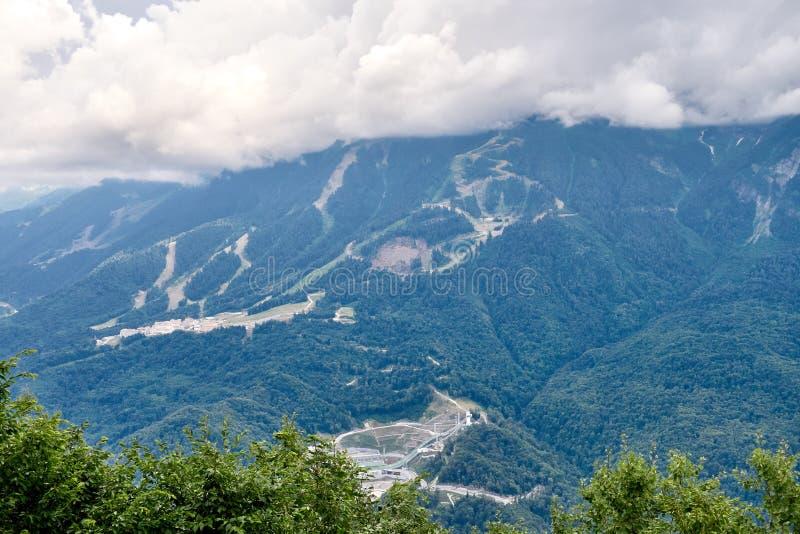Sportanlagen und Wohngebäude auf die Steigung eines hohen Berges mit einer grünen Steigung und die Oberseite in den Wolken Sport lizenzfreie stockbilder
