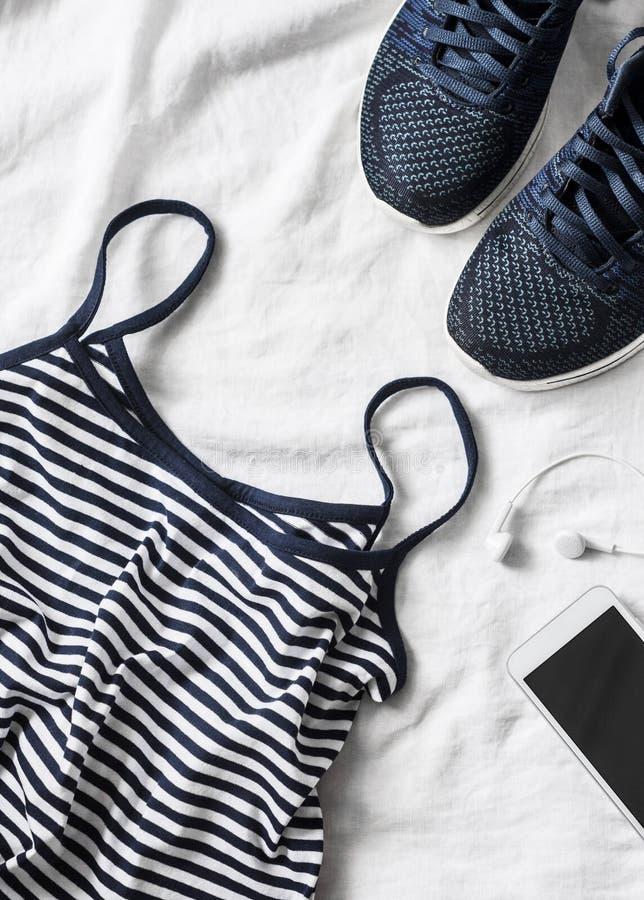Sportar för kvinna` som s beklär på en ljus bakgrund Ärmlös tröja för sportkvinna` s med tunna spagettiremmar, randiga rinnande g royaltyfria foton