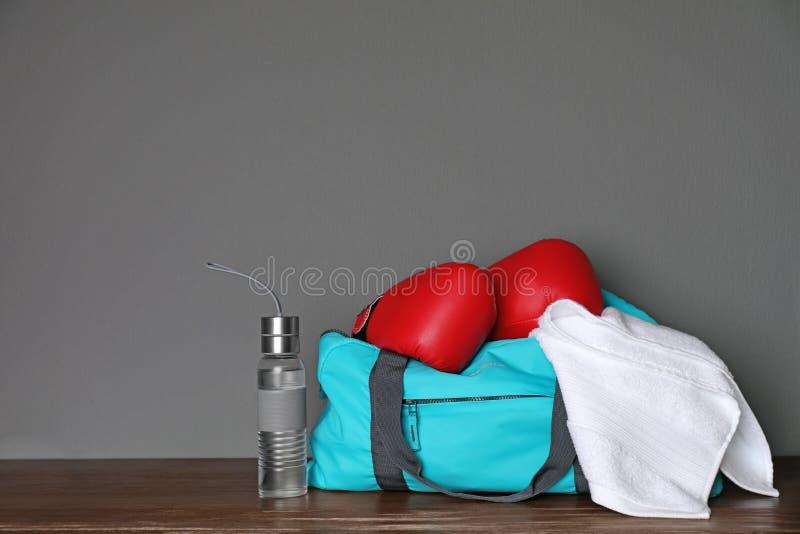 Sportar hänger löst, boxninghandskar, handduken och flaskan arkivbild