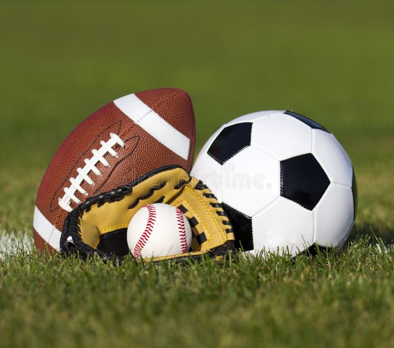 Sportar klumpa ihop sig på fältet med gårdlinjen. Fotbollboll, amerikansk fotboll och baseball i gul handske på grönt gräs arkivbilder