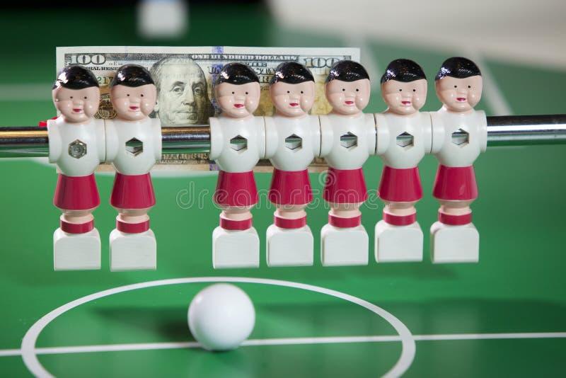 Sportar och pengarbegrepp-leksak fotbollsspelare står i fältet och sedeln i hundra dollar på en bakgrund royaltyfria bilder