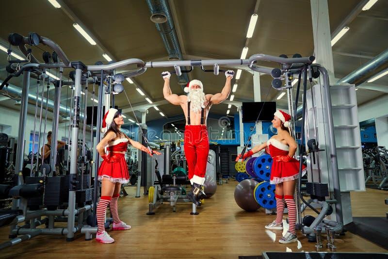 Sportar Santa Claus med flickor i dräkter för jultomten` s i idrottshallen royaltyfri bild