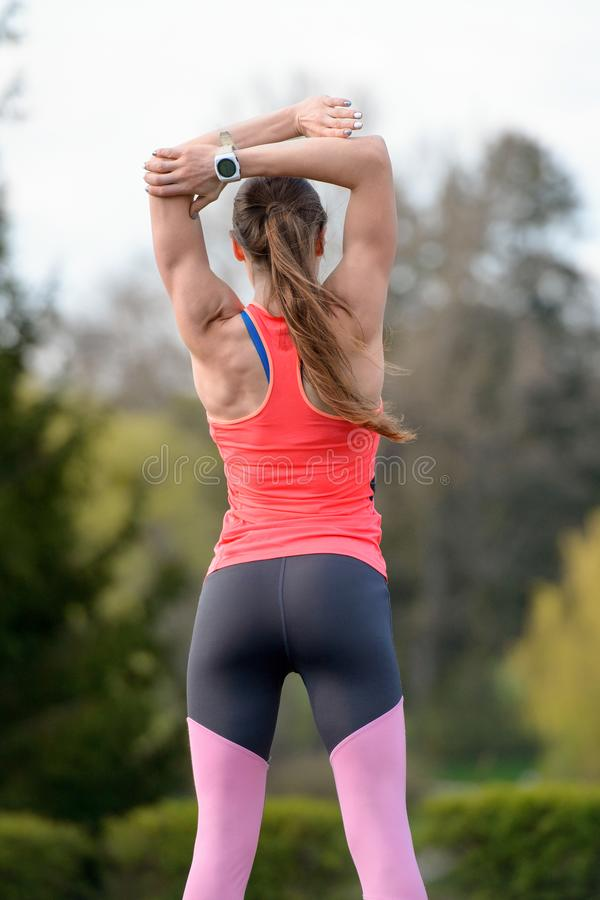 Sportar som kvinnan gör sträckning av övningar på, parkerar utomhus royaltyfria foton