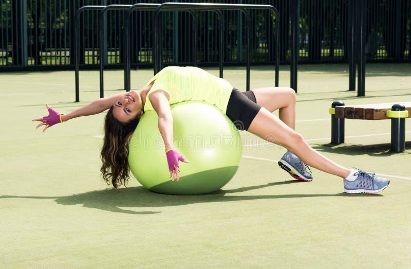 Sportar som utbildar, utomhus Härlig ung kvinna som ligger på bollen royaltyfria bilder