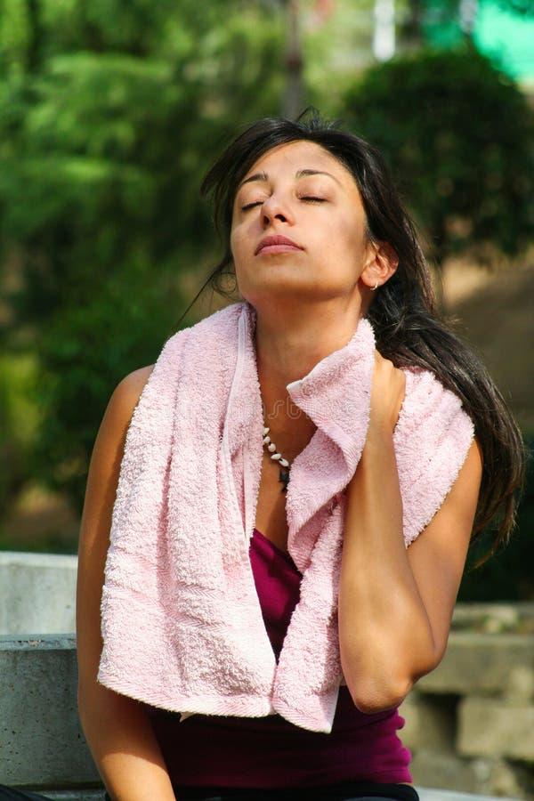 Sportar svett och kopplar av Sportig konditionkvinna med handduken utomhus royaltyfri fotografi