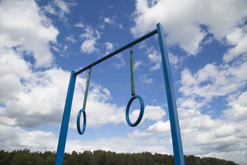 Sportausrüstungsquerlatte mit zwei Ringen auf dem Hintergrund eines Waldes der Wolken des blauen Himmels stockbild