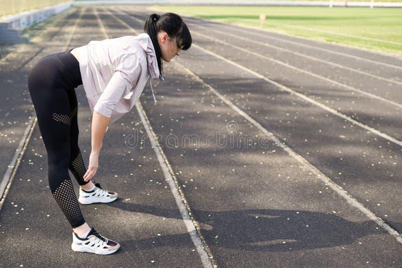 Sportbakgrund med kopieringsutrymme kvinnaidrottsman nen som utomhus gör övningar sund livsstil f?r begrepp royaltyfri bild