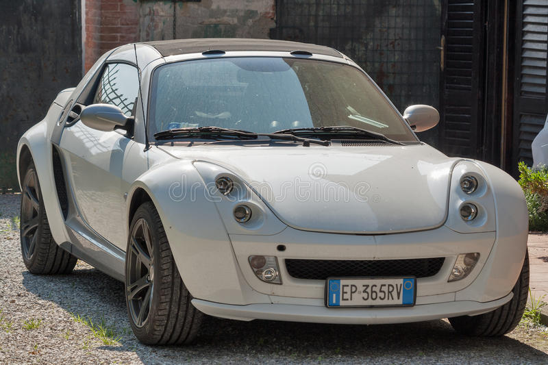 Sportcar Smart Roadster coupe outdoor in Pisa, Italy. White coupe sportcar Smart Roadster in the back yard closeup. Two-door two-seater sports car was first royalty free stock image