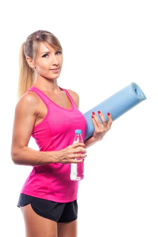 Sportconcept - mooie slanke sportieve vrouw met yogamat en wat stock afbeeldingen
