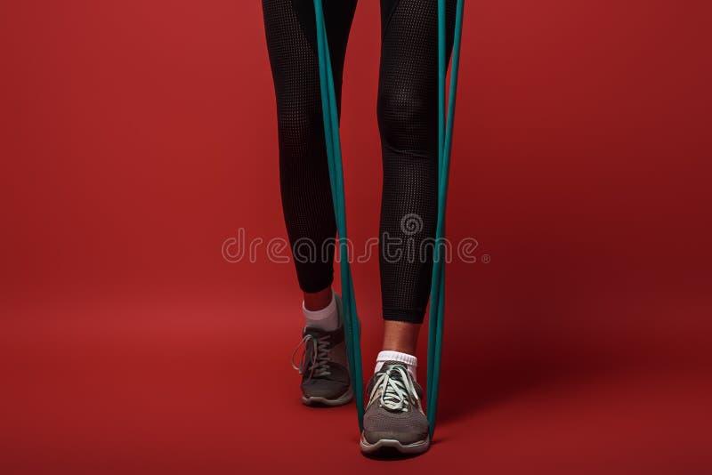 Sporten är livsföringen Stäng sig upp av kvinnan med expanderen som övar över röd bakgrund arkivbilder