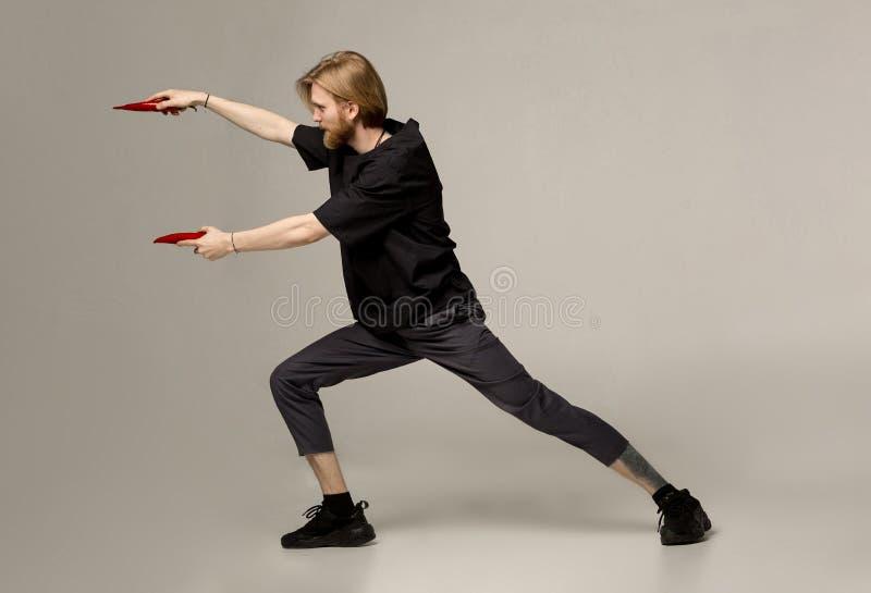 Sporten en gevechtsconcept Kerel het stellen in karate stelt met twee Spaanse pepers in handen stock foto's