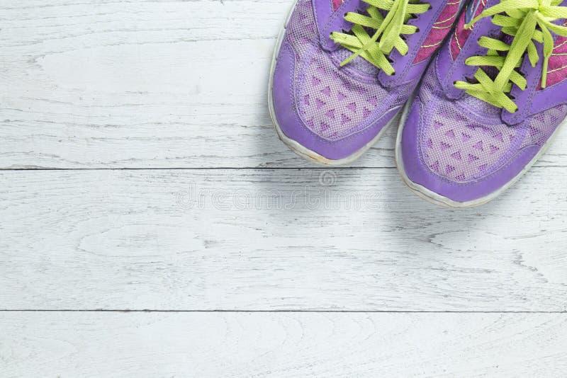 Sporten lägger framlänges purpurfärgade skor på vit träbakgrund med copyspace för din text Sund livsstil för begrepp och att bant royaltyfria foton