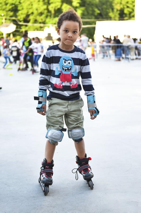 Sporten lurar att försöka att åka skridskor i parkera i staden Gullig pojkeska royaltyfria bilder