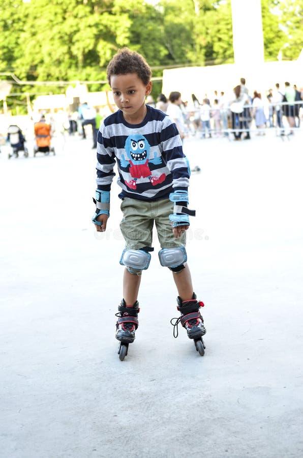 Sporten lurar att försöka att åka skridskor i parkera i staden Gullig pojkeska royaltyfria foton