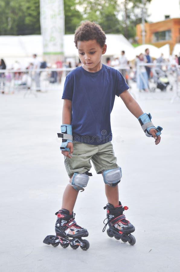 Sporten lurar att försöka att åka skridskor i parkera i staden Gullig pojkeska royaltyfri bild