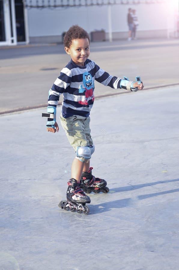 Sporten lurar att försöka att åka skridskor i parkera i staden Gullig pojkeska arkivbild