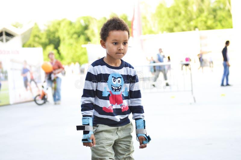 Sporten lurar att försöka att åka skridskor i parkera i staden Gullig pojkeska arkivfoton