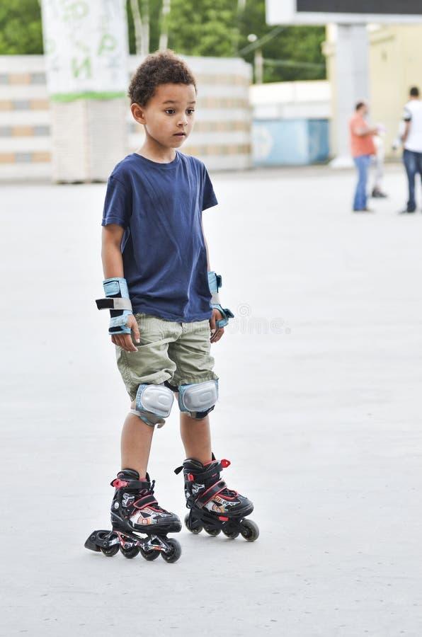 Sporten lurar att försöka att åka skridskor i parkera i staden Gullig pojkeska arkivbilder