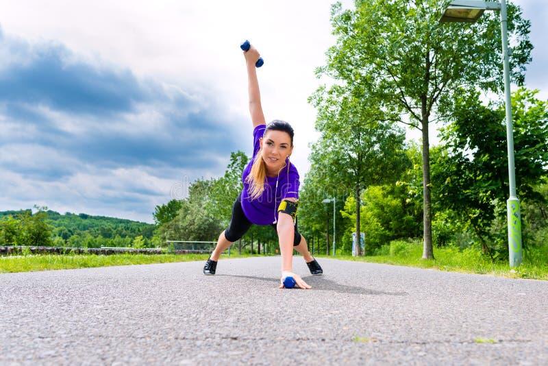 Sporten openlucht - jonge vrouw die fitness in park doen royalty-vrije stock foto's