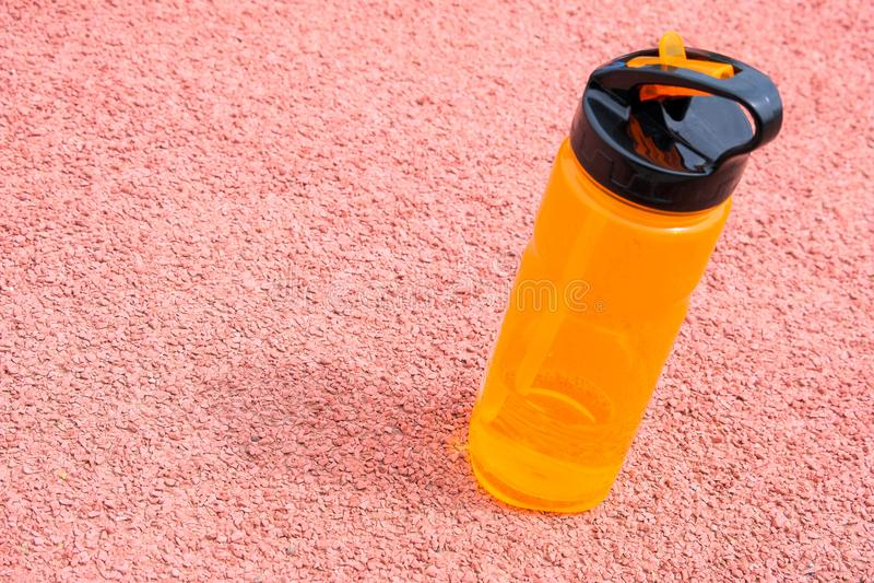 Sporten oranje fles met drinkwater op een roze oppervlakte Natuurlijk zonnig zacht licht stock foto's