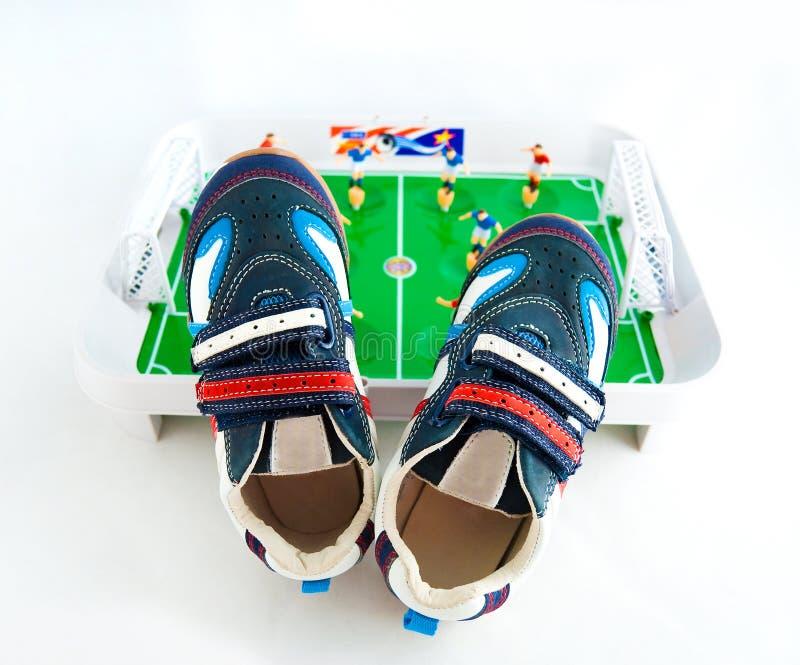sporten schoeisel tegen een stuk speelgoed voetbalgrond royalty-vrije stock foto's