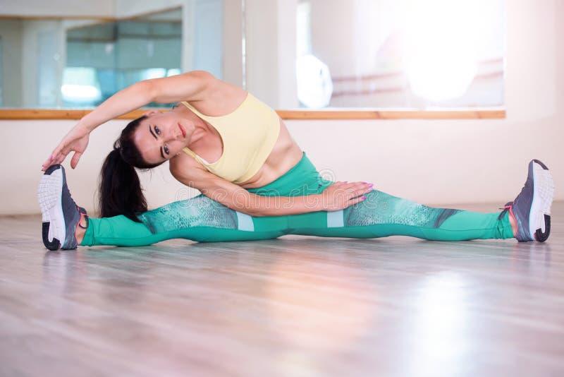 sporten Vrouw bij de gymnastiek die uitrekkende oefeningen doet en op de vloer glimlacht stock afbeeldingen