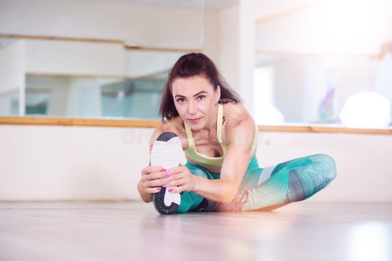 sporten Vrouw bij de gymnastiek die uitrekkende oefeningen doet en op de vloer glimlacht royalty-vrije stock afbeelding