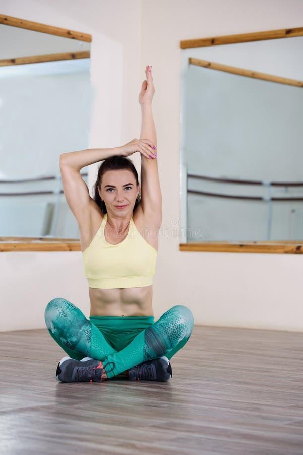 sporten Vrouw bij de gymnastiek die uitrekkende oefeningen doet en op de vloer glimlacht stock foto
