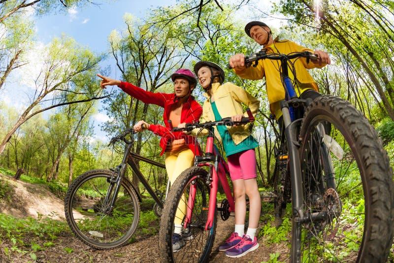 Sportenfamilie die de manieren van de bergfiets zoeken royalty-vrije stock foto