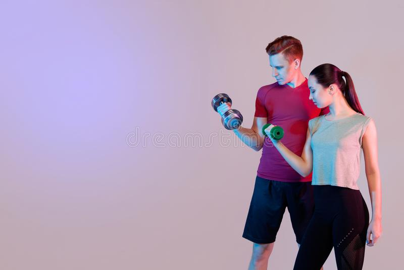 Sportenmeisje en kerel die oefeningen doen Houd domoren, leid de bicepsen op Donkere achtergrond, ruimte voor tekst stock afbeeldingen
