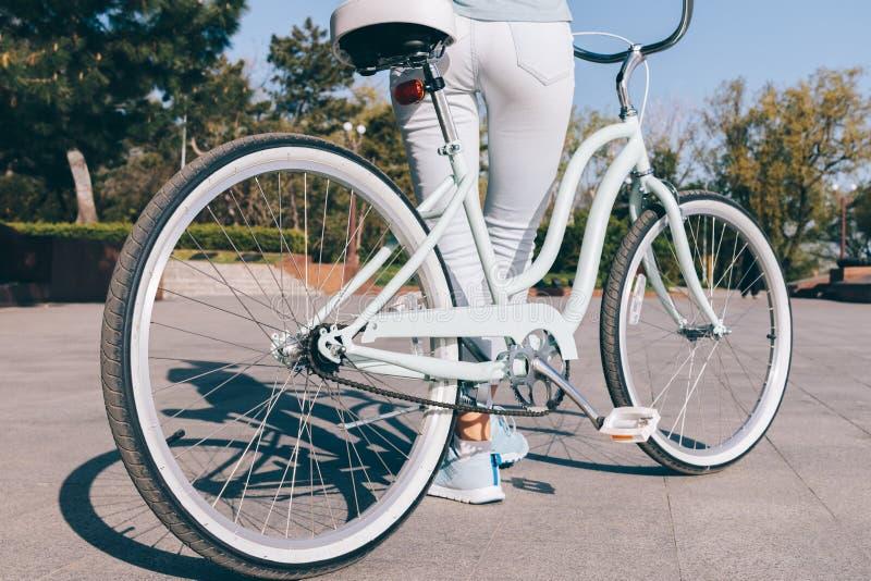 Sportenmeisje in jeans en tennisschoenen die zich dichtbij een fiets bevinden stock afbeelding