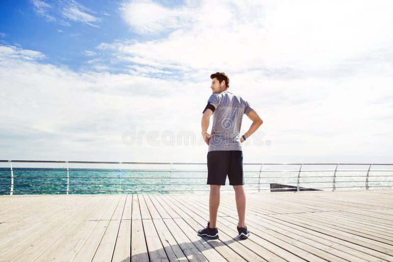 Sportenmens die dichtbij overzees zich in openlucht bevinden stock afbeelding