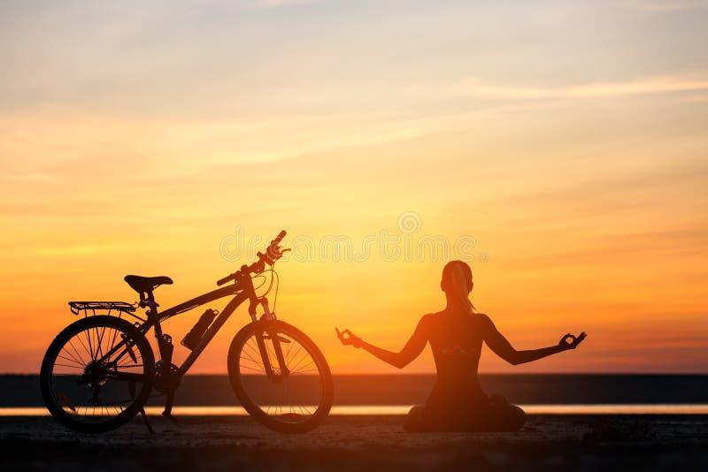 Sportenvrouw die yoga doen bij zonsopgang op het overzeese strand tegen de achtergrond van oranje hemel en fiets Het concept van  royalty-vrije stock fotografie