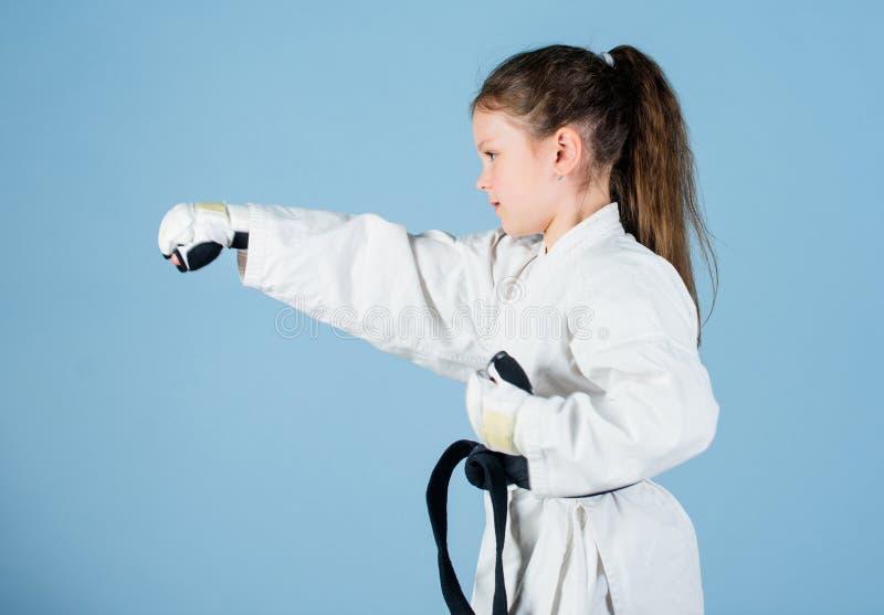 Sporterfolg im Einzelkampf ?bendes Kung Fu Gl?ckliche Kindheit wenig M?dchen in der Gisportkleidung kleines M?dchen in Kriegs stockbild