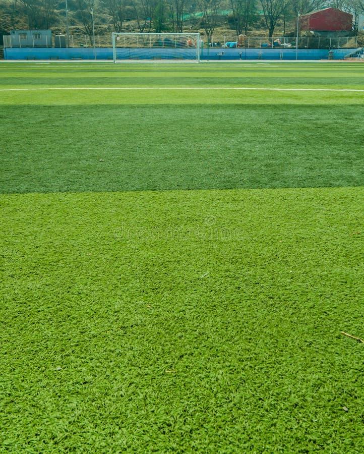 Sportfält som täckas med grönt konstgjort gräs arkivfoton