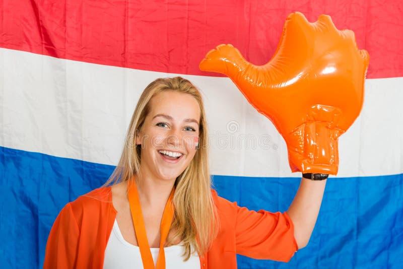 Sportfan, der eine aufblasbare orange Hand zujubelt in vorderem O trägt lizenzfreie stockfotografie