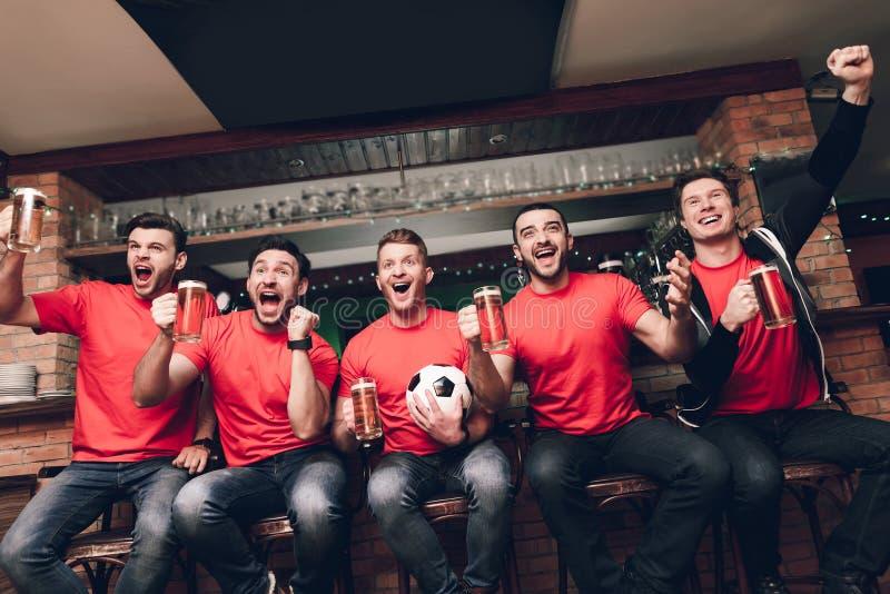 Sportfans, die in feierndem und zujubelndem trinkendem Bier der Linie am Sportbar sitzen stockfotografie