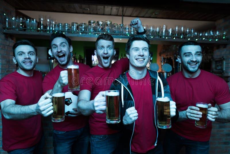 Sportfans som framme firar och hurrar av tv som dricker öl på sportstången royaltyfri foto