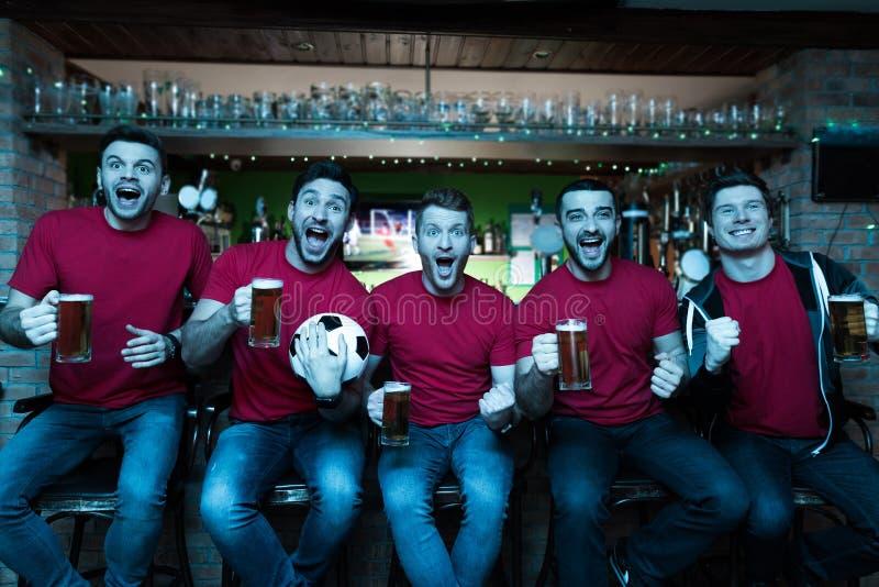 Sportfans som framme firar och hurrar av tv som dricker öl på sportstången fotografering för bildbyråer