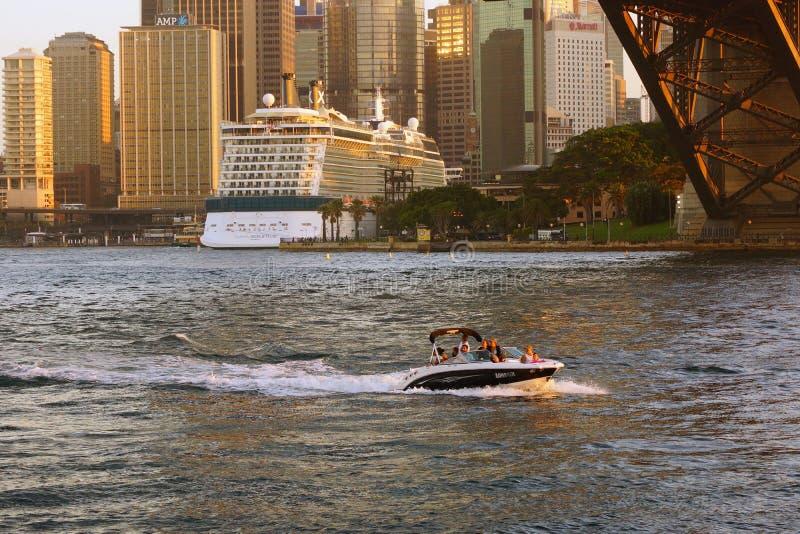 Sportfartyg under Sydney Harbour Bridge och kryssningfartyg i den runda kajen, Australien royaltyfri bild
