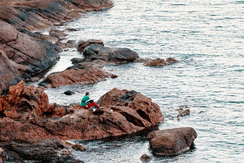 Sportfiskarefiskaren som sitter på, vaggar och fiskar med stänger nära sjösidan royaltyfria bilder