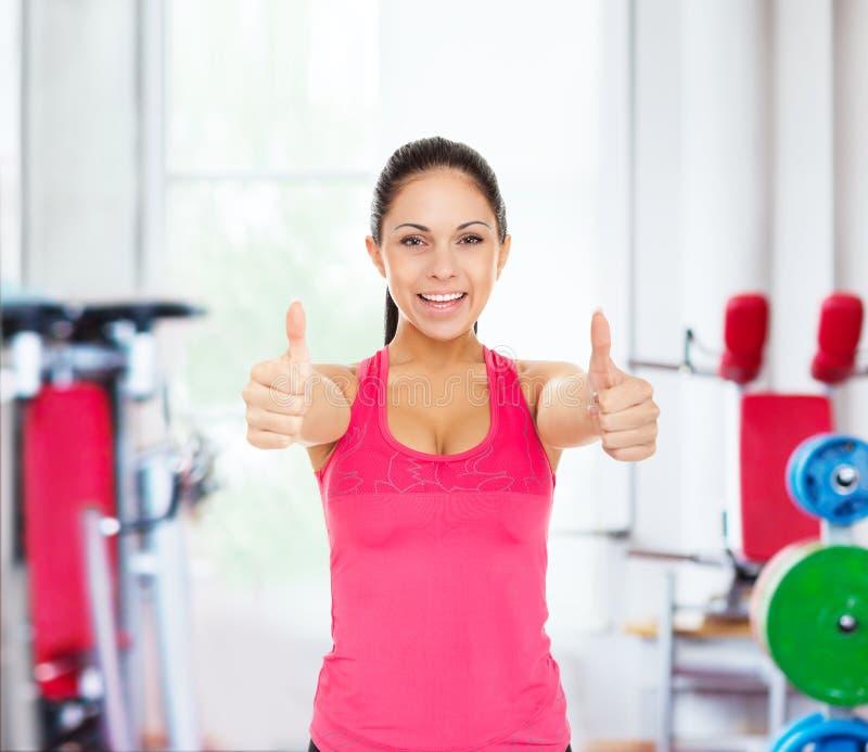 Sportfitness de vrouwenglimlach toont duim op gymnastiek royalty-vrije stock afbeeldingen