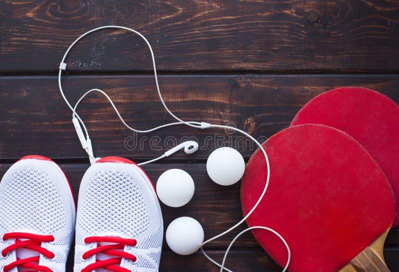 Sportfitness, het concept van het gewichtsverlies Pingpongracket, ballen, tennisschoenen, oortelefoons op donkere houten achtergr royalty-vrije stock afbeelding