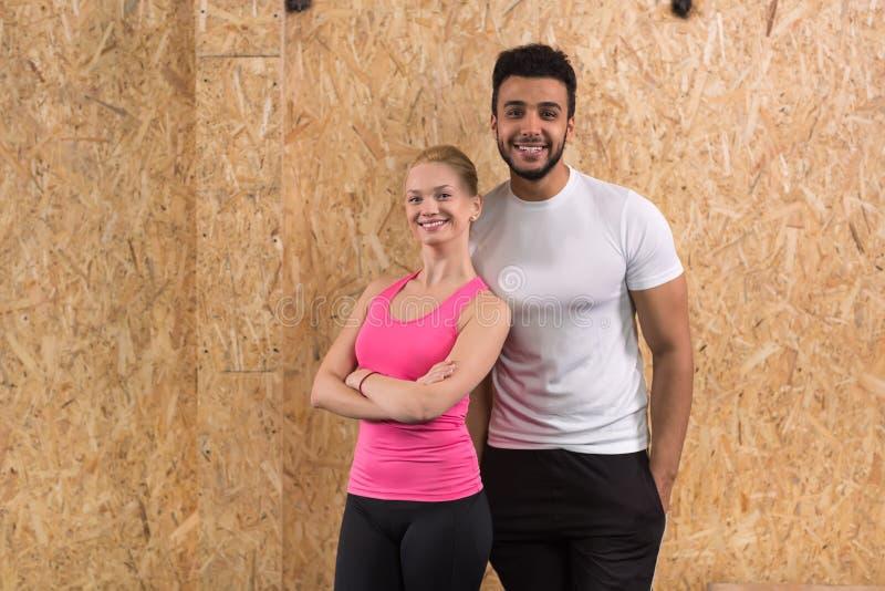 Sportfitness Paar, Jonge Gezonde Man en het Binnenland die van de Vrouwengymnastiek Oefeningen doen royalty-vrije stock fotografie