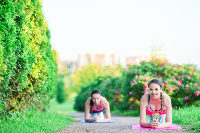 Sportfitness vrouwen die opdrukoefeningen opleiden Vrouwelijke atleet die duw op buitenkant in leeg park uitoefenen Het geschikte stock afbeelding