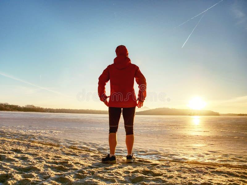 Sportflicka i vinterkläder som bort kör till horisonten av det iskalla havet arkivfoto