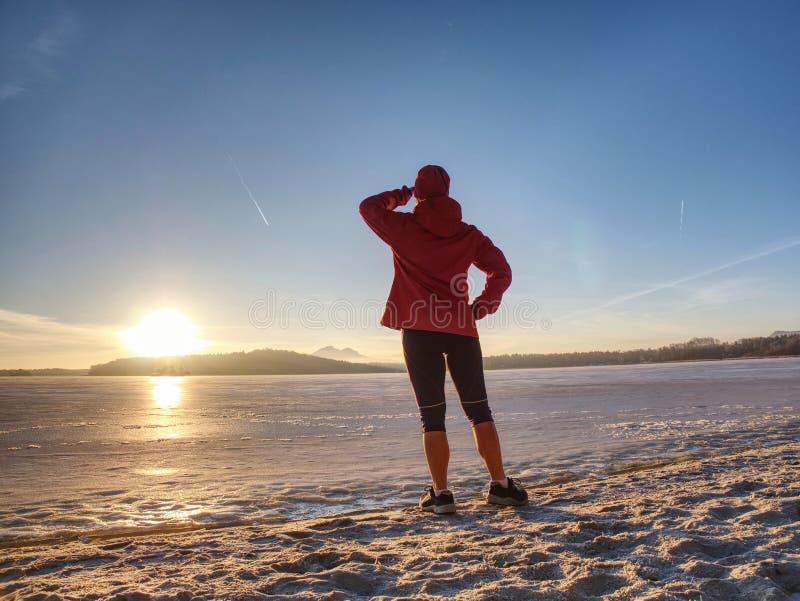 Sportflicka i vinterkläder som bort kör till horisonten av det iskalla havet arkivbilder