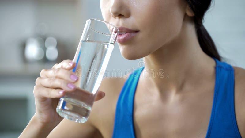 Sportflicka som dricker kristallklart vatten som återställer aquajämvikt, når utbildning arkivfoton